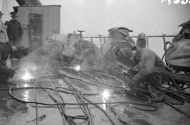 [Welders at work in the rain on the deck of a boat]