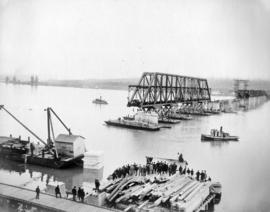[A crowd gathers to watch a span of the bridge being floated into place]