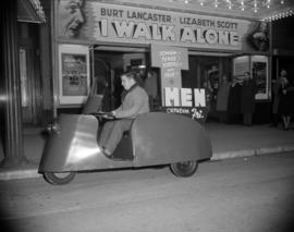 [Man driving a 3-wheeler in front of the Orpheum Theatre]