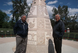 Two men standing at a public monument to Chinese Canadians in Calgary