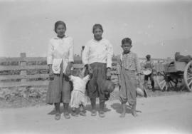 Four children standing on road holding hands