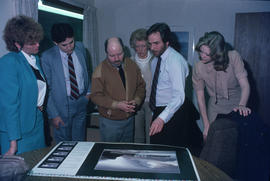 Toni Onley (centre) and group examine his Centennial Art Series print at Agency Press