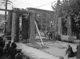 Men using crane to erect Lumberman's Arch on Pender Street near Hamilton Street, for visit of Duk...