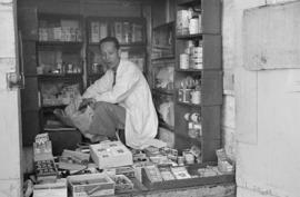[Chinese merchant inside tiny store]