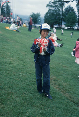 Boy holding Canadian flags during the Centennial Commission's Canada Day celebrations