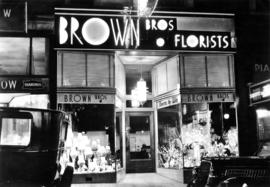 [Brown Bros. Florists' store front at 655 Granville at night with neon sign]