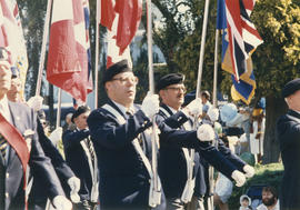 Men in uniform marching with flags