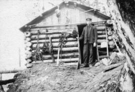 [Man outside log cabin with rifle, traps, and other hunting equipment]