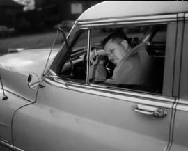 [Man asleep in car with his head resting on the steering wheel taken as a still for a film produc...