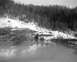 [Partially constructed Coquitlam Dam, looking east at edge of tree covered hillside]