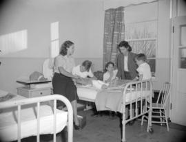 [Two women from the Junior League playing with children on a hospital ward]