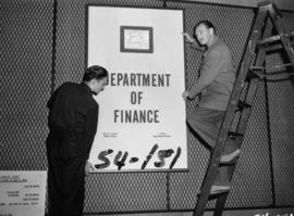 Department of Finance display sign being hung in P.N.E. B.C. building