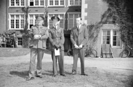 [Two airforce men with a civilian outside a building probably the airforce training school]
