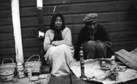 [Unidentified indigenous woman and man sitting with baskets and carvings]