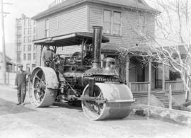 [Two men posing with a City of Vancouver steam roller on Pender Street]
