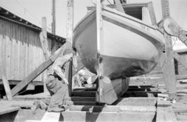 Karl Koenig working on boat in front of Harbour Marine Service building