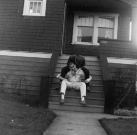 Two men on front steps of house