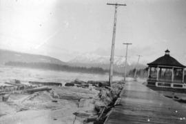 [View of Kitsilano Beach during a storm, showing wooden sidewalk, bandstand, and driftwood washed...