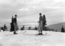Two skiers looking at a view of Point Grey and Stanley Park from the top of Mt. Seymour, B.C.