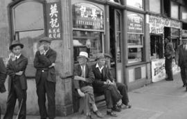 [Men sitting outside shallow building at Pender and Carrall Streets]