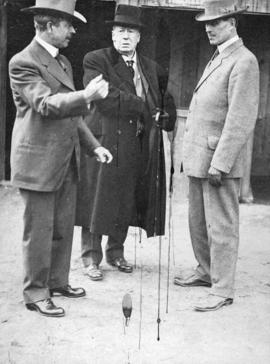 [L.D. Taylor standing with two men at sports field]