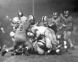 [A player is tackled during the 43rd Grey Cup game at Empire Stadium]