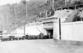 [Mine entrance showing miners and linked carts]