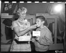 Woman feeds boy award-winning baking entry in 1957 P.N.E. Home Arts competition