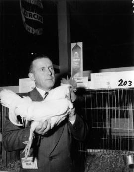 Man with award-winning rooster in 1955 P.N.E. Poultry and Pet Stock competition