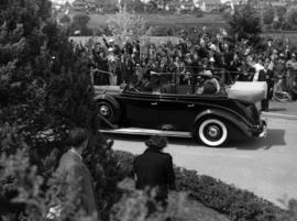 [King George VI and Queen Elizabeth being driven through crowd-lined street]