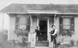 [A.B. Forrest and his wife in front of their house on the corner of Renfrew Street and 1st Avenue]