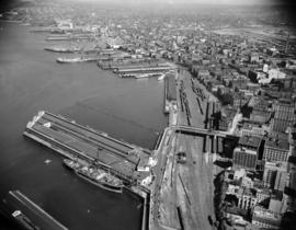 [Aerial view of Vancouver showing piers along the waterfront looking east]