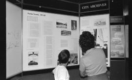 Woman and boy viewing the Vancouver City Archives' display, Portholes and Pilings
