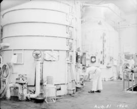 Worker taking sample from large tank