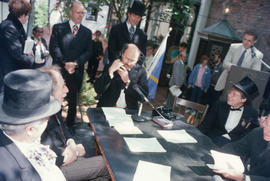 Mayor Harcourt speaking into telephone during reenactment of Vancouver's first City Council meeti...