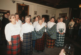 Group of women wearing kilts singing and holding a piece of the Centennial tartan fabric