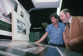Toni Onley (right) and man examine his Centennial Art Series print at Agency Press