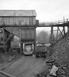 [Trucks in loading area under a wooden mining structure]