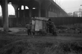 [Men moving a shack on a cart near the Georgia Viaduct]
