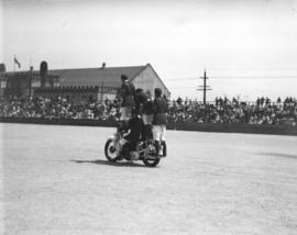 [Four stunt riders on a motorcycle on the Beatty Street drill grounds]