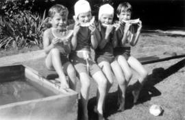 John Banfield, Jane Banfield, Alix Louise Gordon, and unknown girl eating watermelon by swimming ...