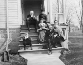 [A group of adults and children sitting on the steps of a house]