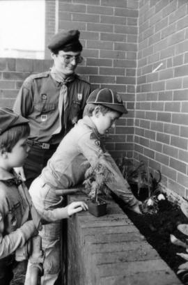 Boy Scouts and leader gardening