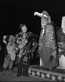 [Lord Alexander in full First Nations dress receiving a plaque from Chief William Scow during a c...
