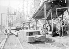 [Men producing lumber with machinery in forest]