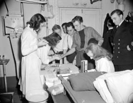 [Red Cross workers testing blood of sailors at a donor clinic on board the H.M.C.S. Warrior]