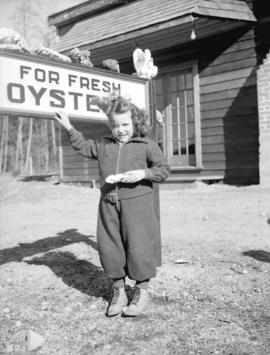 [A girl posing by a sign for oysters at] Oyster Bay