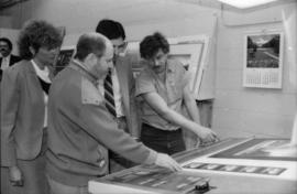 Toni Onley (left) and group examine Centennial Art Series print at Agency Press
