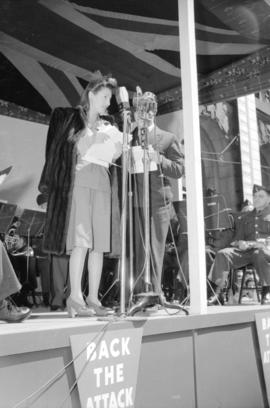 [Barbara Stanwyck on stage giving a speech to promote the Canadian bond drive]