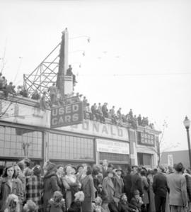 [Crowds on top of the Bowell-MacDonald car dealership building and on the street waiting to watch...